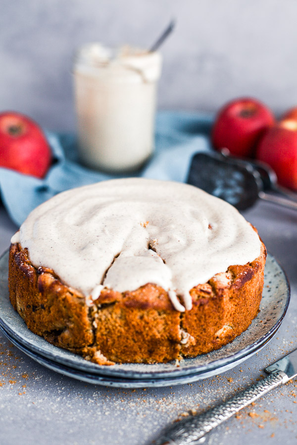 Apple and Almond Cake with creamy cashew frosting, with a slice cut out