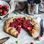 Rustic Vegan Strawberry Galette on a gray surface with a slice cut out, Maja Brekalo
