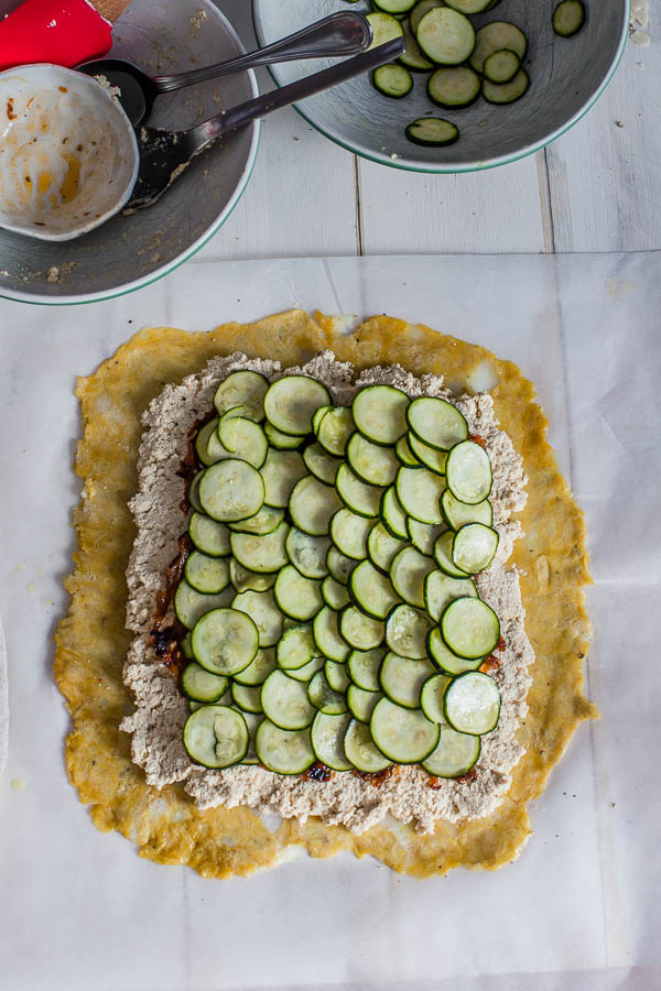rolled out pie pastry with tofu filling, caramelized onion and zucchini slices