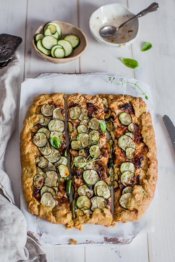 caramelised onion zucchini galette on wooden white background