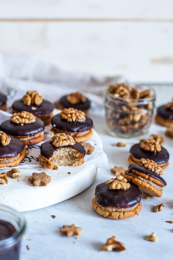 Hazelnut sandwich cookies with walnut filling and chocolate glaze on a white chopping board