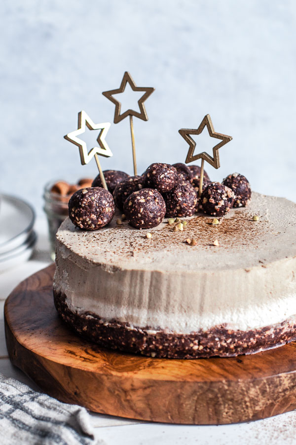 Unbaked Vegan Mocha Cake decorated with golden stars and chocolate bliss balls